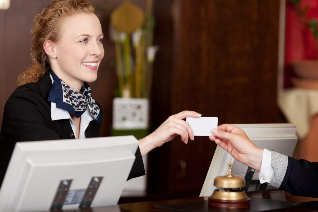 The receptionist smiles and gives the guest a room access card
