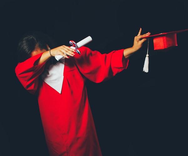 Student w czerwonej todze, cieszący się ze zdobycia dyplomu.