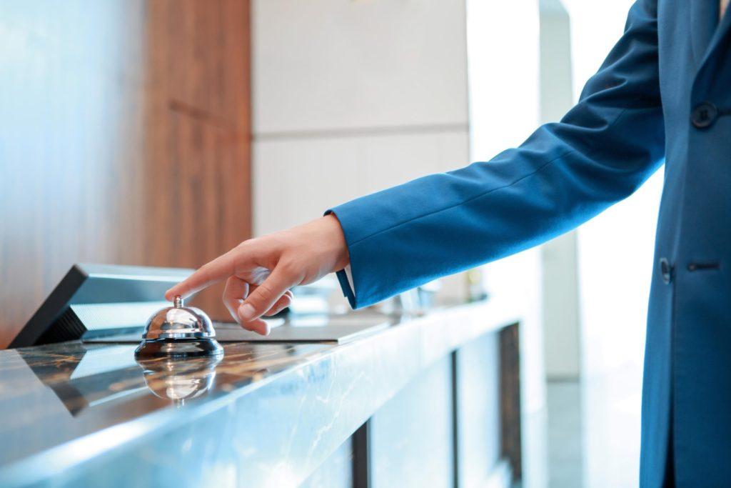 Kalendarz rezerwacji pokoi w hotelu - mężczyzna naciska dzwonek na recepcji